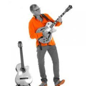nic orange skjorte spiller el gitar med klasssisk i stativ4343-0018n-r